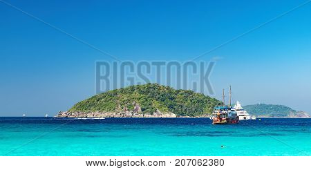 View from the beach to the crystal blue water of the Andaman Sea and Similan Island, Thailand. Tourist boats and the island on the horizon sea cruise in tropical waters