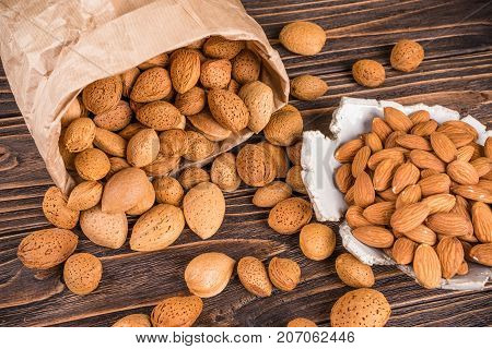 dreed almonds on wooden background in bag