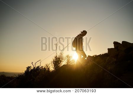 bearded hiker with backpack walking up hill during sunset