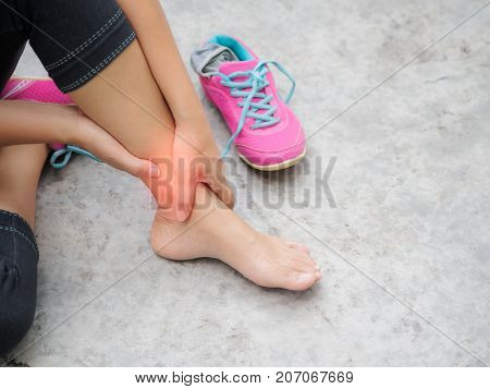 Woman suffering from an ankle injury while exercising. Running sport injury concept.