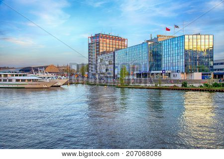AMSTERDAM, NETHERLANDS - MAY 5, 2016: modern buildings on embankment of Amstel river in Amsterdam, Netherlands near Amsterdam Central Station (Centraal)