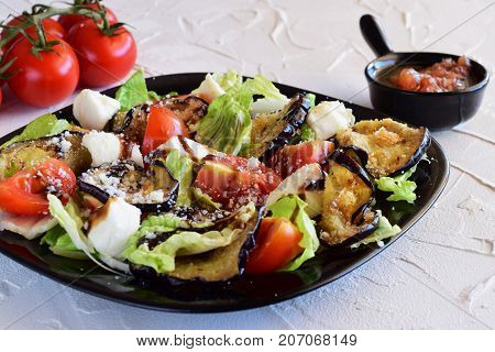 Aubergine salad with tomatos, mozzarela, iceberg lettuce with balsamic glace vinegar and olive oil on a black plate on a white concrete background. Healthy eating. Meditteranean lifestyle
