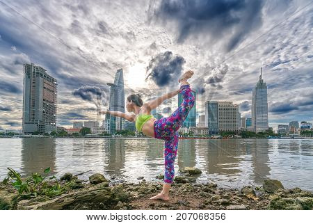 Ho Chi Minh City, Vietnam - September 25, 2017: Young attractive woman in yoga posture, wearing sportswear bra and pants, outdoor sunset, urban riverside in Ho Chi Minh City, Vietnam