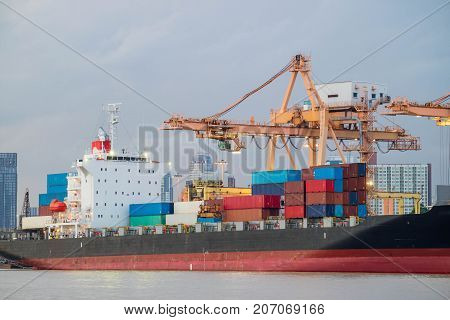 Shipping trade port. Container cargo ship loading or unloading by crane bridge. Logistics industrial and transportation business background