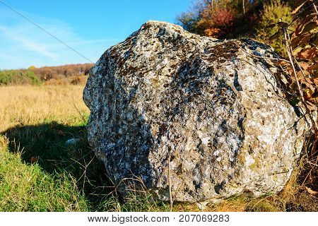 Close-up Background Of The Big Gray Stone Overgrown By Moss On The Background Of Autumn Field