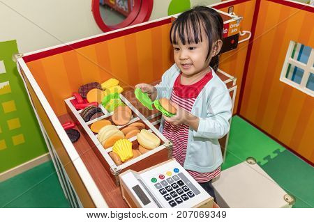Asian Chinese Little Girl Role-playing At Burger Store