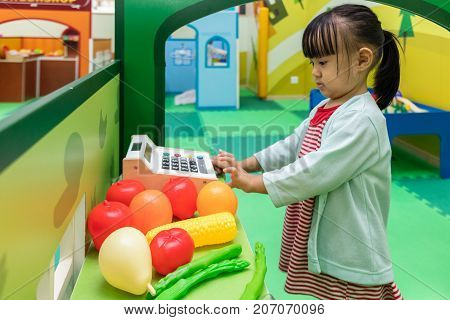 Asian Chinese Little Girl Role-playing At Fruits Store