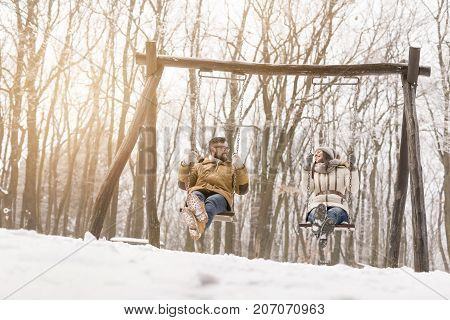 Beautiful young couple sitting on a swing and having fun on a snowy winter day
