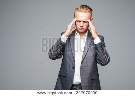Sad Man In Gray Suit Touching His Temples Because Of Suffering From Migraine On Gray Background