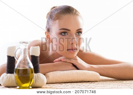 Young, beautiful and healthy woman relaxing in spa salon. Traditional oriental aroma therapy and massaging treatments with herbal balls and oil.