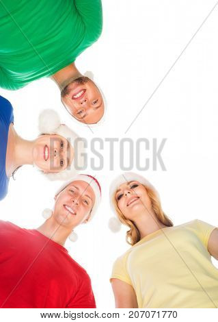 Group of smiling friends in Christmas hats embracing together. Isolated white background. New Year, Xmas, X-mas celebrating concept.