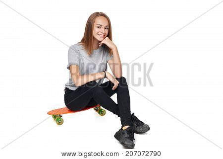 Teen girl in full length sitting on skate board smiling at camera, isolated on white background