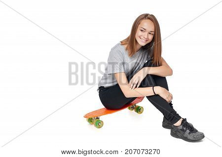 Teen girl in full length sitting on skate board smiling looking away at blank copy space, isolated on white background