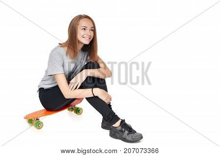 Teen girl in full length sitting on skate board smiling looking up at blank copy space, isolated on white background