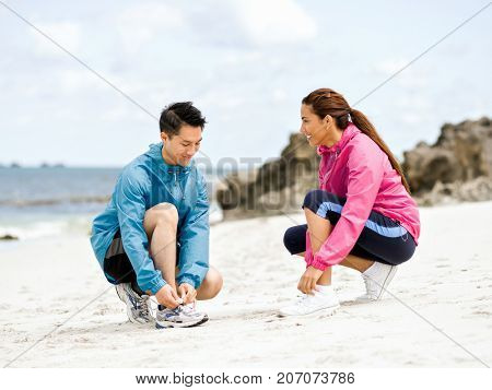 Young couple of runners tying shoelace at the seaside