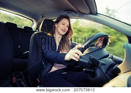 Young female driver driving small passenger car