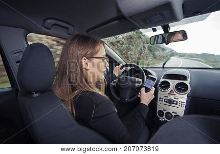 Young female driver using cellphone to text message while driving a car