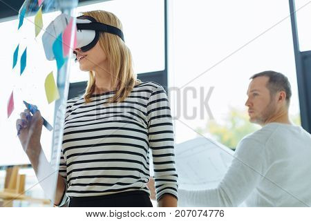 Ready to write. Delighted pleasant blonde woman holding a highlighter and being ready to write while being in a virtual reality