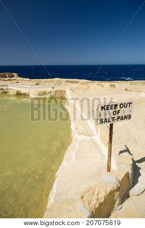 Old abandoned salt pans, a rusty caution sign, and horizon over sea at Gozo island, Malta