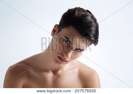 Naked model. Attractive male model bowing head and demonstrating his naked body while posing on camera