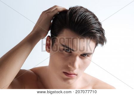Nice hair dress. Handsome male pressing lips and putting right hand on his head while looking forward
