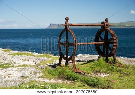 Old corroded iron winder with cogwheel, next to the sea, irish coast