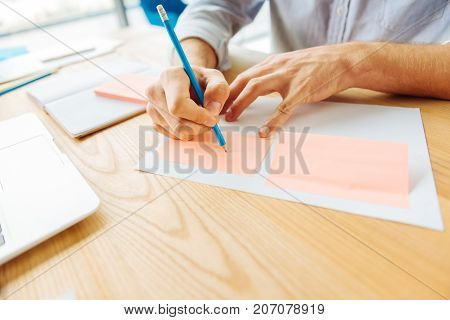 Sign here. Competent office worker using pencil while making notes and sitting at his workplace