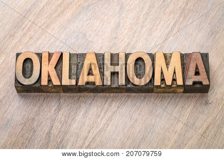 Oklahoma word abstract in vintage  letterpress wood type against grained wooden background