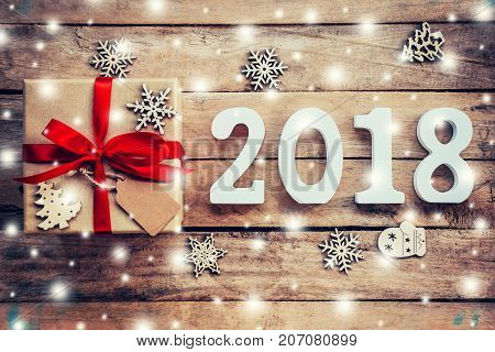 Wood Numbers Forming The Number 2018, For The New Year 2018 On Rustic Wooden With Gift Box And Snow