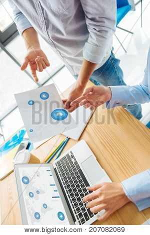 Modern technologies. Female hands being on laptop, competent man pointing at document while standing near his colleague