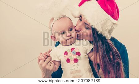 Christmas family holiday concept. Mother wearing santa claus hat holding and hugging baby in aureole.