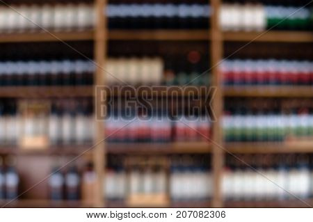Blurred image of wine shelves display in supermarket. Defocused Rows of Wine Liquor bottles on the store shelf. Alcoholic beverage abstract background. Alcohol drink market concept.