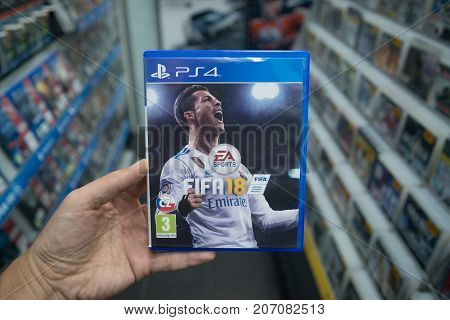 Bratislava, Slovakia, october 2 2017: Man holding Fifa 18 videogame on Sony Playstation 4 console in store