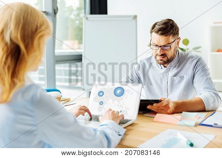 Connected with work. Competent brunette keeping smile on his face and leaning elbows on table while reading article