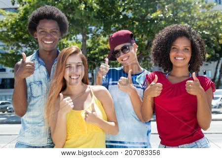 Multi ethnic group of latin and african american and caucasian young adults showing thumb outdoor in the summer in the city