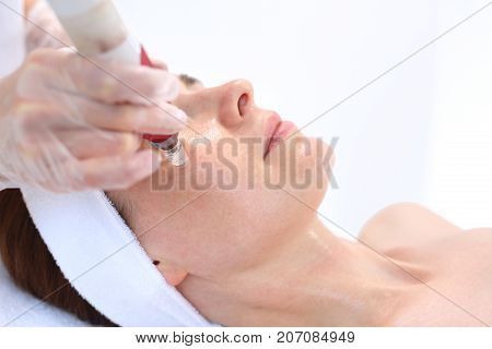 Needle mesotherapy, Beautician performs a needle mesotherapy treatment on a woman's face poster