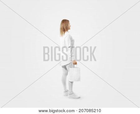 Woman holding blank white craft paper bag design mockup. Person hold kraft textured purchase pack mock up isolated. Clear shop bagful branding template. Shopping carry package in mans arm.