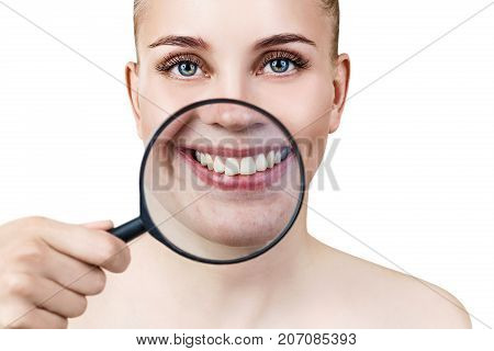 Young woman with magnifying glass presents her perfect white teeth. Heathy smile concept. Over gray background.