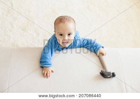 Cute baby boy standing near the couch, is keeping hammer and intend to work