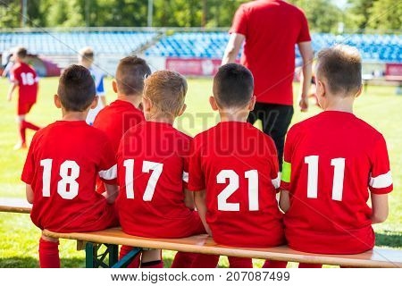 Kids Soccer Team. Youth Football Players with Soccer Coach. Young Substitute Player Sitting on Wooden Bench.
