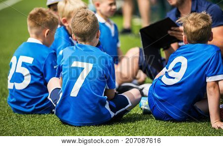 Coach is giving kids soccer team pre-game talk. Children soccer training match. Sport motivational lecture for kids