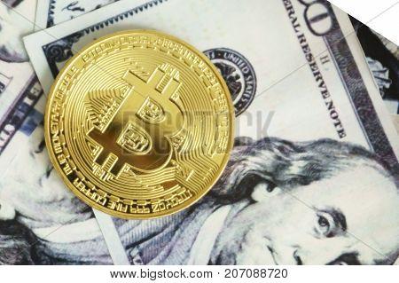 Gold coin bitcoin on hundred dollar bills close up