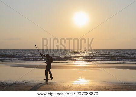 Goa India - February 10 2016: Unidentified man spinning pole on the beach.