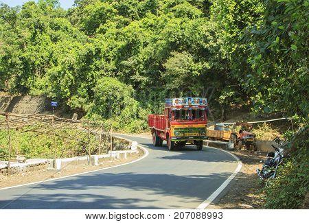 Goa India - February 13 2016: Multicolored Indian truck TATA is driving along the mountain road