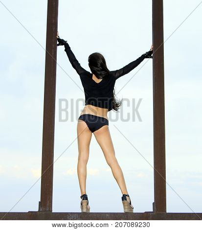 Back view of young girl posing on the rusty structures over blue sky