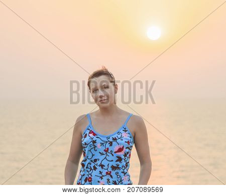 Pretty young female against beauty sunset on sea