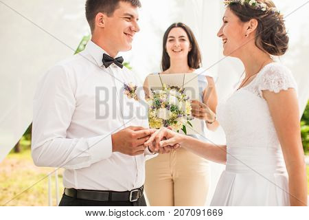 Brides, where the groom wears a ring on a bride's finger. Focus on hands