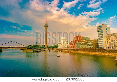 Looking at Media Harbor at Rhine-River in Dusseldorf in Germany. Media Harbor with Rhine-Tower and famous buildings in gentle sunset light with their reflection in the water. Beautiful and colorful cityscape of the german city