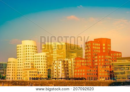 Looking at Media Harbor at Rhine-River in Dusseldorf in Germany. Media Harbor with Rhine-Tower and famous buildings in gentle sunset light. Beautiful and colorful cityscape of the german city