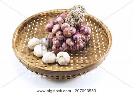 Shallots and garlic in wooden basket isolated on white background.